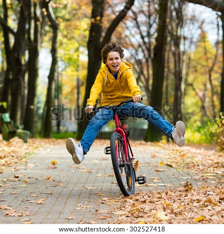 Urban biking - teenage boy riding bike in city park  - stock photo