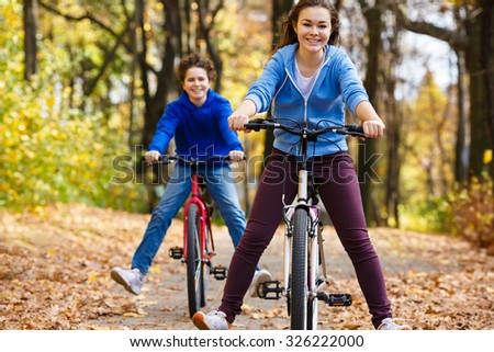 Urban biking - teens riding bikes in city park  - stock photo