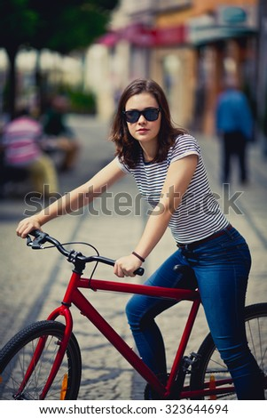 Urban biking - woman and bike in city  - stock photo