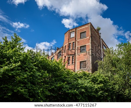 Urban brick building isolated by green bushes.