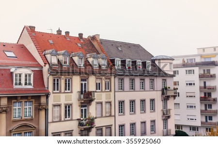 Urban building with a red tile roof balconies with flower beds in city Strasbourg autumn - stock photo