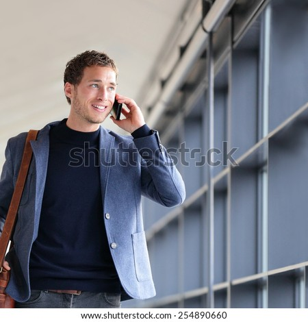 Urban business man talking on smart phone traveling walking in full body length inside in airport. Casual young businessman wearing suit jacket and shoulder bag. Handsome male model in his 20s. - stock photo