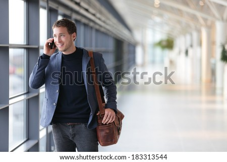 Urban business man talking on smart phone traveling walking inside in airport. Casual young businessman wearing suit jacket and shoulder bag. Handsome male model in his 20s. - stock photo