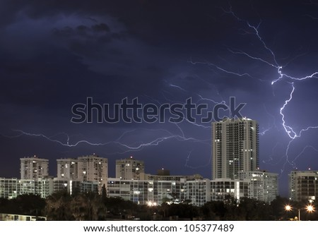 Urban city night scene with large lightning bolt lighting up the cloudy stormy sky.