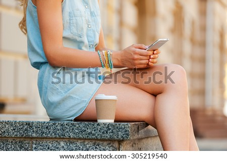 Urban connection. Close-up of young woman holding mobile phone while sitting outdoors - stock photo