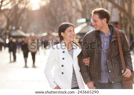 Urban couple walking on La Rambla Barcelona arm in arm. Romantic laughing lovers talking holding hands on date. Young multicultural couple Asian and Caucasian on La Rambla Barcelona, Catalonia, Spain. - stock photo