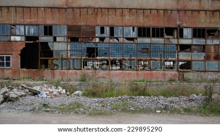Urban decay series. Abandoned plant building exterior with broken windows - stock photo