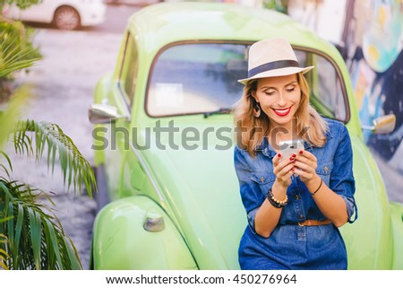 Urban fashion and technology. Pretty young woman using smartphone while leaning on the car on the street. - stock photo