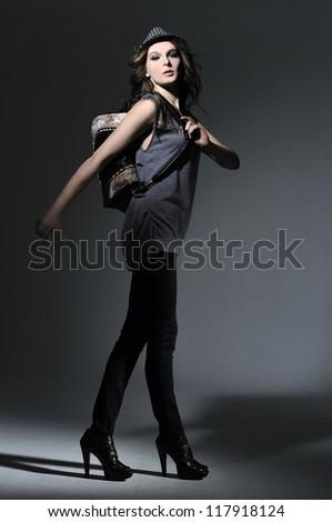 Urban fashion girl with modern bag posing on light background - stock photo