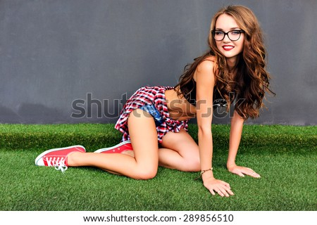 Urban fashion portrait of stylish sexy hipster woman with amazing fit slim sportive body, street style outfit and glasses, warm sunny colors, cute emotions, joy, party. - stock photo