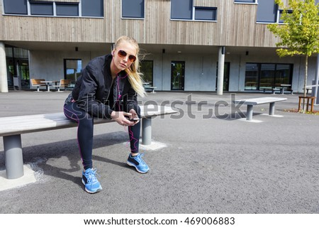 Urban female in workout outfit uses phone outdoor