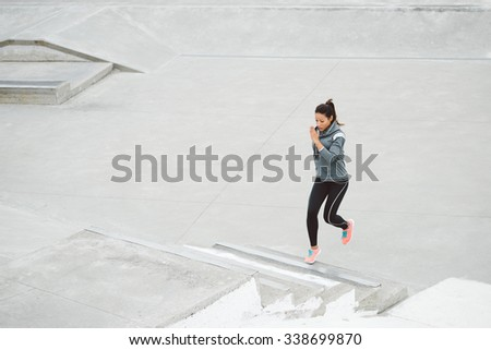 Urban fitness woman running and climbing stairs for legs power and strength training. Female athlete working out outdoor. - stock photo