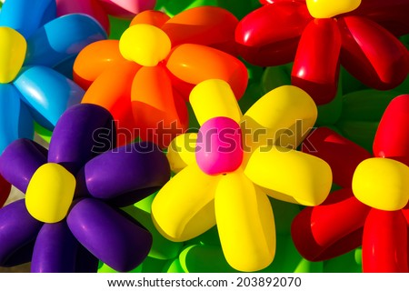 Urban Flowers. Closeup view of a bunch of inflatable toy flowers of different colors. Merry holidays! Be happy! - stock photo