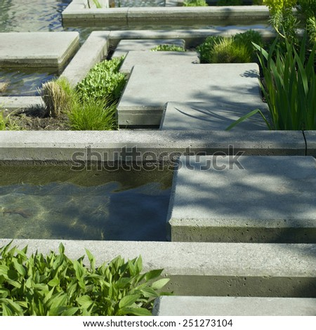 Urban garden water feature of concrete and vegetation - stock photo