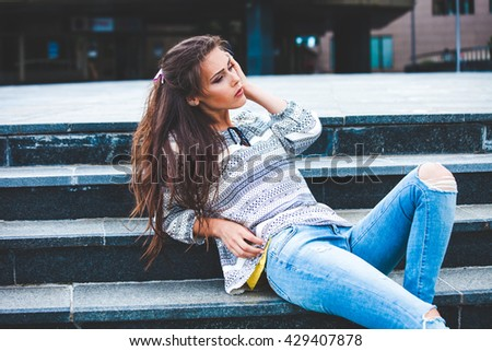 urban girl portrait on stairs in blue jeans and shirt - stock photo