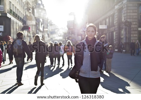 Urban girl standing out from the crowd at a city street. - stock photo