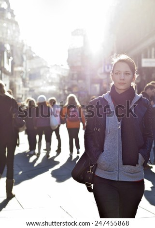 Urban girl standing out from the crowd at a city street - stock photo
