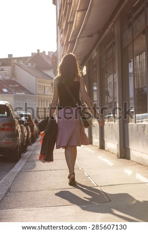 Urban girl striding through a city street on a sunny day. - stock photo
