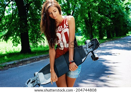 urban girl with longboard outdoors in summer  - stock photo