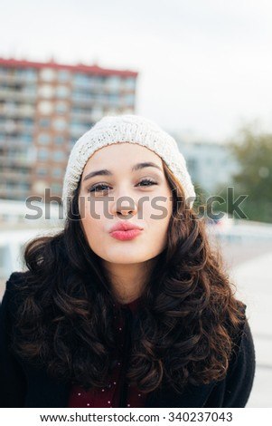 Urban girl with woolen cap kissing to camera in the city