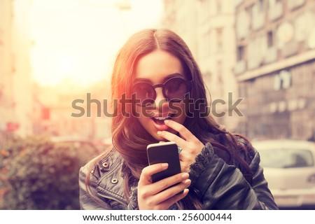 Urban girl writing a message. - stock photo