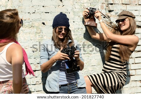 Urban girls have fun with vintage photo cameras outdoor near grunge wall, filtered - stock photo