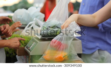 Urban green market series/buyer collecting plastic bag of produce with scale in the background - stock photo