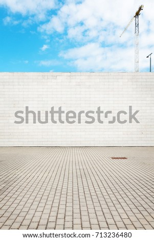 Urban grungy street wall with construction crane behind it, may be used as background or texture