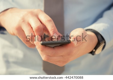 Urban guy / businessman with a cellphone outdoors. Shallow depth of field.