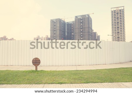 Urban High Rise Buildings Under Construction Behind Security Fence Barrier