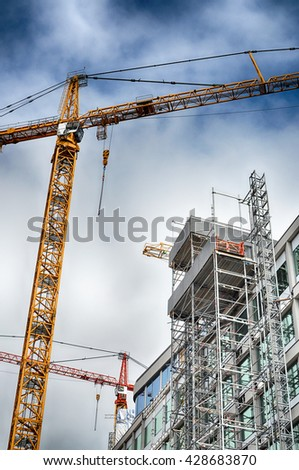 Urban highrise building under construction with crane. - stock photo