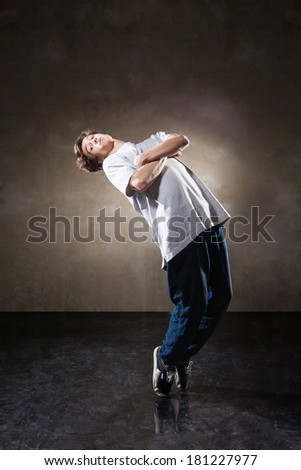 urban hip hop dancer with grunge concrete wall background texture jumping and dancing