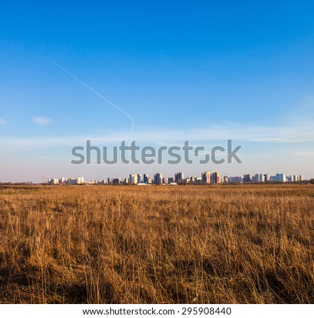 Urban landscape. Dry field and high-rise buildings of Kyiv (Ukraine) in the distance. - stock photo