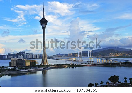 Urban landscape of Macau with famous traveling tower under blue sky near river in Macao, Asia.
