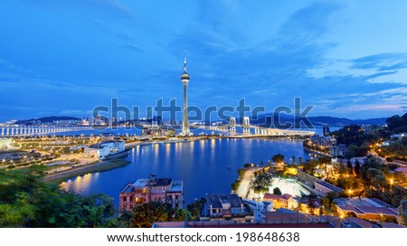 Urban landscape of Macau with famous traveling tower under blue sky near river in Macao, Asia.  - stock photo