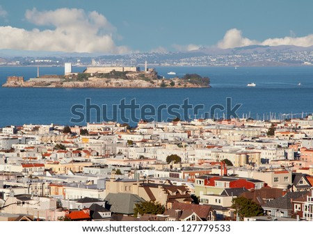 Urban landscape with San Francisco roofs, blue water and Alcatraz island.