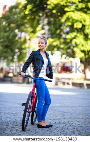 Urban leisure - young woman and bike in city  - stock photo