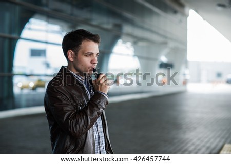 Urban lifestyle portrait of a man vaping near the airport before registration with custom vape mod device.