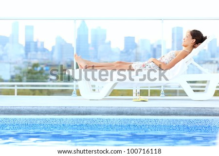 Urban luxury city lifestyle woman lying by pool relaxing in sun lounger during summer in Montreal, Quebec, Canada. - stock photo