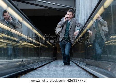 urban man calling on the phone on an escalator - stock photo