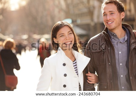 Urban modern young professionals couple walking romantic laughing talking holding hands on date. Young multicultural couple Asian and Caucasian on La Rambla Barcelona, Catalonia, Spain. - stock photo