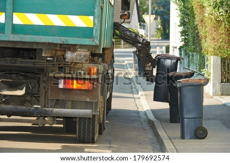 urban municipal recycling garbage collector truck loading waste and trash bin - stock photo