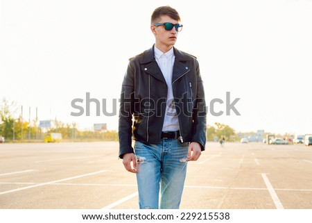 Urban outdoor portrait of young stylish man wearing leather biker jacket and sunglasses, evening sunlight. Posing at countryside parking. - stock photo