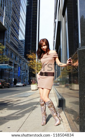 urban outfit, fashion brunette girl in leopard sexy boots posing in big city