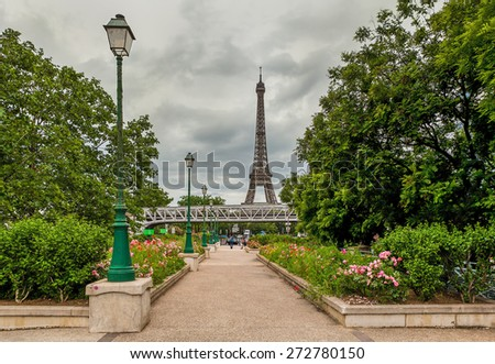 Urban park with green trees, flowers and lampposts as Eiffel Tower on background in Paris, France. - stock photo