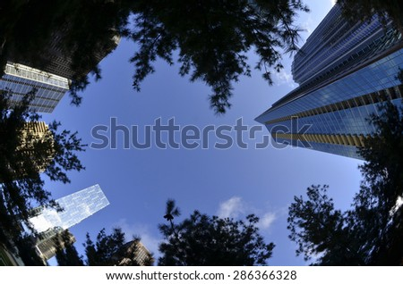 Urban Park with tall buildings skyscrapers and sky - stock photo