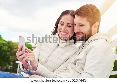 urban photo of young adult couple looking at cellphone and smiling
