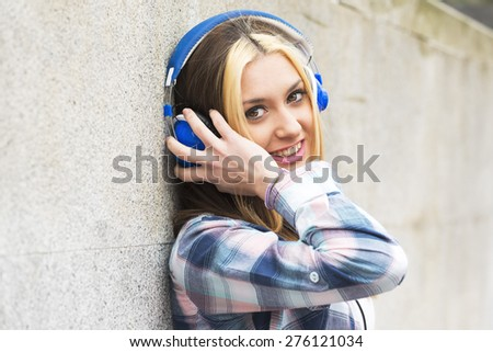 Urban portrait beautiful cheerful girl with headphones listening music . - stock photo