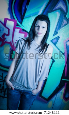 Urban portrait of a beautiful young brunette girl with graffiti background, serious facial expression