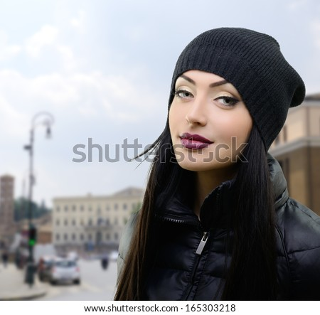 urban portrait of beautiful young woman in black hat and jacket over city landscape - stock photo